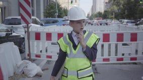 Πορτρέτο ενός σκεπτικού μικρού παιδιού που φορούν τον εξοπλισμό ασφάλειας και του σχεδίου οικοδόμησης εκμετάλλευσης κρανών κατασκ απόθεμα βίντεο