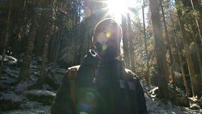 Πορτρέτο ενός σοβαρού γενειοφόρου φωτογράφου ατόμων με ένα σακίδιο πλάτης και μια κάμερα που στέκονται σε ένα κωνοφόρο χειμερινό  απόθεμα βίντεο