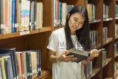 Πορτρέτο ενός σοβαρού νέου σπουδαστή που διαβάζει ένα βιβλίο σε μια βιβλιοθήκη στοκ εικόνες με δικαίωμα ελεύθερης χρήσης