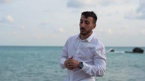Πορτρέτο ενός στοχαστικού επιτυχούς γενειοφόρου νεαρού άνδρα που στέκεται στην παραλία και που εξετάζει το ρολόι του Νέες στάσεις απόθεμα βίντεο