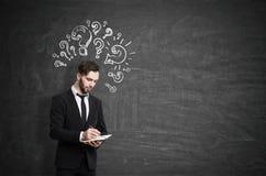 Πορτρέτο ενός στοχαστικού επιχειρηματία σε ένα μαύρο κοστούμι που στέκεται κοντά σε έναν πίνακα κιμωλίας με τα ερωτηματικά που επ Στοκ Φωτογραφία