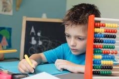Πορτρέτο ενός σχολικού αγοριού που εργάζεται στην εργασία math Στοκ Φωτογραφία