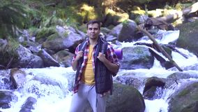 Πορτρέτο ενός τουρίστα ατόμων στο δάσος ενάντια σε έναν ποταμό βουνών φιλμ μικρού μήκους