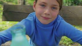 Πορτρέτο ενός υγιούς παιδιού με ένα ποτήρι του γάλακτος Ένα αγόρι είναι πόσιμο γάλα στη φύση κατανάλωση υγιής απόθεμα βίντεο