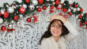 Πορτρέτο ενός φωτεινού σγουρού brunette ενάντια στο σκηνικό του ντεκόρ Χριστουγέννων με τις ασημένιες και σκοτεινές σφαίρες απόθεμα βίντεο