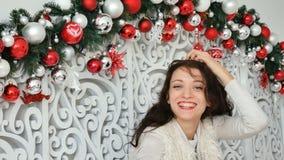 Πορτρέτο ενός φωτεινού σγουρού brunette ενάντια στο σκηνικό του ντεκόρ Χριστουγέννων με τις ασημένιες και σκοτεινές σφαίρες φιλμ μικρού μήκους