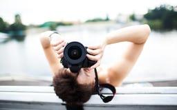 Πορτρέτο ενός φωτογράφου που καλύπτει το πρόσωπό της με τη κάμερα Στοκ Εικόνες