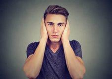 Πορτρέτο ενός χαλαρωμένου ατόμου που καλύπτει τα αυτιά του που εξετάζουν τη κάμερα Μην ακούστε καμία κακή έννοια άνθρωπος συγκινή στοκ φωτογραφία με δικαίωμα ελεύθερης χρήσης