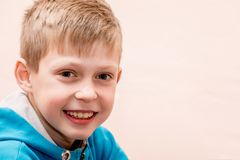 Πορτρέτο ενός χαμογελώντας αγοριού κοντά επάνω σε ένα μουτζουρωμένο ρόδινο υπόβαθρο, στοκ φωτογραφία