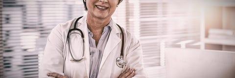 Πορτρέτο ενός χαμογελώντας θηλυκού γιατρού που στέκεται με τα όπλα που διασχίζονται στοκ φωτογραφία με δικαίωμα ελεύθερης χρήσης