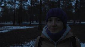 Πορτρέτο ενός χαμογελώντας κοριτσιού σε ένα κρύο σκοτεινό χειμερινό δάσος φιλμ μικρού μήκους