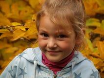 Πορτρέτο ενός χαμογελώντας κοριτσιού σε ένα υπόβαθρο των φωτεινών κίτρινων φύλλων στοκ φωτογραφία