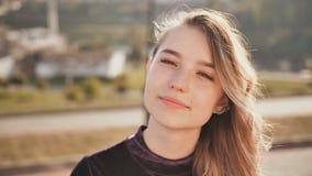 Πορτρέτο ενός χαμογελώντας κοριτσιού στο υπόβαθρο της πόλης μια θερινή ημέρα απόθεμα βίντεο
