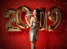 Πορτρέτο ενός χαμογελώντας νέου έκπληκτου κοριτσιού στο χρυσό λαμπρό φόρεμα που παρουσιάζει κιβώτιο δώρων και που εξετάζει τη κάμ στοκ εικόνες