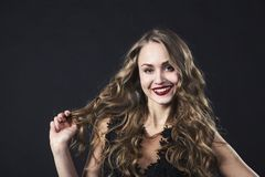 Πορτρέτο ενός χαμογελώντας νέου κοριτσιού σε ένα φόρεμα δαντελλών σε ένα μαύρο υπόβαθρο στοκ εικόνες