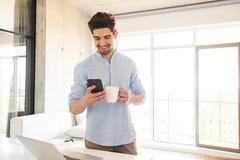 Πορτρέτο ενός χαμογελώντας νεαρού άνδρα που χρησιμοποιεί το κινητό τηλέφωνο Στοκ εικόνα με δικαίωμα ελεύθερης χρήσης