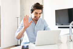 Πορτρέτο ενός χαμογελώντας νεαρού άνδρα στα ακουστικά Στοκ φωτογραφία με δικαίωμα ελεύθερης χρήσης