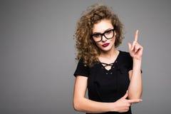 Πορτρέτο ενός χαμογελώντας κοριτσιού που δείχνει το δάχτυλο επάνω στο copyspace που απομονώνεται σε έναν γκρίζο Στοκ Εικόνες