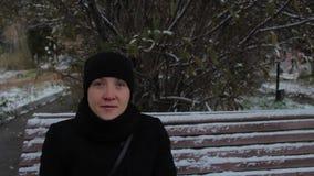 Πορτρέτο ενός χαμογελώντας κοριτσιού σε ένα μαύρο φόρεμα, που κάθεται σε έναν πάγκο το χειμώνα φιλμ μικρού μήκους