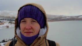Πορτρέτο ενός χαμογελώντας κοριτσιού σε ένα σακάκι με μια κουκούλα στη θάλασσα απόθεμα βίντεο