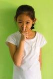 Πορτρέτο ενός χαμογελώντας νέου κοριτσιού με το δάχτυλό της πέρα από το στόμα της Στοκ Εικόνες