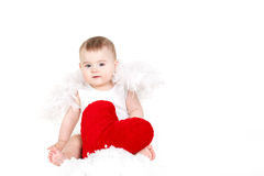 Πορτρέτο ενός χαριτωμένου λατρευτού μικρού αγγέλου βαλεντίνων με την κόκκινη μαλακή καρδιά που απομονώνεται στο άσπρο υπόβαθρο Στοκ Εικόνα