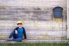 Πορτρέτο ενός χαριτωμένου εύθυμου αγοριού με την κίτρινη συνεδρίαση ΚΑΠ υπαίθρια Στοκ φωτογραφία με δικαίωμα ελεύθερης χρήσης
