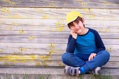 Πορτρέτο ενός χαριτωμένου εύθυμου αγοριού με την κίτρινη συνεδρίαση ΚΑΠ υπαίθρια Στοκ φωτογραφίες με δικαίωμα ελεύθερης χρήσης
