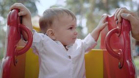 Πορτρέτο ενός χαριτωμένου μικρού παιδιού στο φρέσκο άσπρο πουκάμισο που ταλαντεύεται σε μια παιδική χαρά φιλμ μικρού μήκους