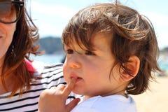 Πορτρέτο ενός χαριτωμένου μωρού που απολαμβάνει το χρόνο του στην παραλία, με το mum στο υπόβαθρο Στοκ Εικόνες