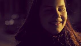 Πορτρέτο ενός χαριτωμένου σκεπτικού χαμογελώντας κοριτσιού εφήβων σε μια οδό πόλεων νύχτας 4K slowmo UHD φιλμ μικρού μήκους