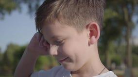 Πορτρέτο ενός χαριτωμένου χαμογελώντας αγοριού υπαίθρια Το λατρευτό παιδί ξοδεύει το χρόνο στο θερινό πάρκο απόθεμα βίντεο