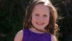 Πορτρέτο ενός χαριτωμένου 5χρονου κοριτσιού με τη μακριά σκοτεινή τρίχα σε ένα θερινό πάρκο φιλμ μικρού μήκους