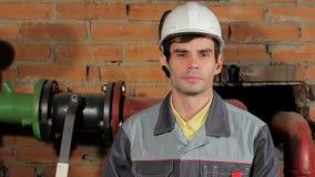 Πορτρέτο ενός όμορφου αρσενικού Καυκάσιος μηχανικός brunette Ένας εργαζόμενος σε ένα χαμόγελο κρανών απόθεμα βίντεο