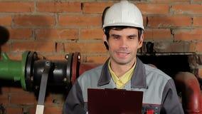 Πορτρέτο ενός όμορφου αρσενικού καυκάσιου γέλιου μηχανικών brunette Ένας εργαζόμενος σε ένα κράνος γελά παρουσιάζοντας δόντια του φιλμ μικρού μήκους