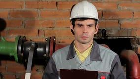 Πορτρέτο ενός όμορφου αρσενικού καυκάσιου μηχανικού brunette σοβαρού Ο εργαζόμενος σε ένα κράνος και μια κινηματογράφηση σε πρώτο απόθεμα βίντεο