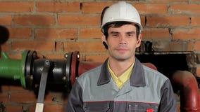 Πορτρέτο ενός όμορφου αρσενικού Καυκάσιο χαμόγελο μηχανικών brunette Ένας εργαζόμενος σε ένα χαμόγελο κρανών που παρουσιάζει δόντ απόθεμα βίντεο