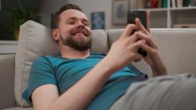 Πορτρέτο ενός όμορφου ατόμου που δακτυλογραφεί και που στο smartphone του στο σπίτι Αρσενικό που χρησιμοποιεί το ψηφιακό κινητό ξ απόθεμα βίντεο