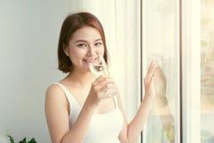 Πορτρέτο ενός όμορφου γυαλιού εκμετάλλευσης γυναικών με το νερό Υγιεινός τρόπος ζωής, χορτοφάγος διατροφή και γεύμα Πιείτε το νερ στοκ φωτογραφίες