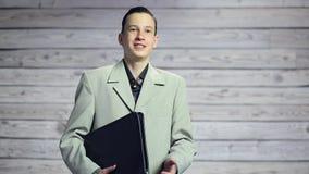 Πορτρέτο ενός όμορφου ευτυχούς χαμογελώντας ατόμου με έναν χαρτοφύλακα στο χαμόγελο χεριών του απόθεμα βίντεο