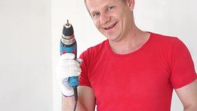 Πορτρέτο ενός όμορφου εύθυμου νέου ευρωπαϊκού οικοδόμου με ένα τρυπάνι στα χέρια του απόθεμα βίντεο
