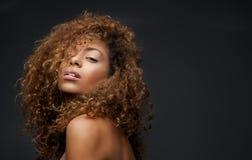 Πορτρέτο ενός όμορφου θηλυκού προτύπου μόδας με τη σγουρή τρίχα