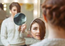 Πορτρέτο ενός όμορφου κοκκινομάλλους κοριτσιού με μακρυμάλλη, ο οποίος κοιτάζει στον καθρέφτη στο σαλόνι ομορφιάς στοκ φωτογραφίες με δικαίωμα ελεύθερης χρήσης