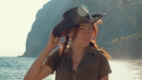 Πορτρέτο ενός όμορφου κοκκινομάλλους ταξιδιωτικού κοριτσιού σε ένα καπέλο κάουμποϋ στην παραλία θάλασσας φιλμ μικρού μήκους