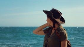 Πορτρέτο ενός όμορφου κοκκινομάλλους ταξιδιωτικού κοριτσιού σε ένα καπέλο κάουμποϋ στην παραλία θάλασσας απόθεμα βίντεο