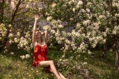 Πορτρέτο ενός όμορφου κοριτσιού μεταξύ του φυλλώματος και των λουλουδιών άνοιξη στοκ φωτογραφία