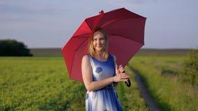 Πορτρέτο ενός όμορφου κοριτσιού με μια κόκκινη ομπρέλα στον πράσινο χορό κοριτσιών χαμόγελου τομέων χλόης συγκινήσεων χαμόγελου η απόθεμα βίντεο