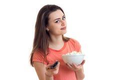 Πορτρέτο ενός όμορφου κοριτσιού με τον τηλεχειρισμό διαθέσιμο, και pop-corn Στοκ Φωτογραφίες