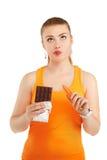 Πορτρέτο ενός όμορφου κοριτσιού που έχει ένα δίλημμα με τη διατροφή της Isolat Στοκ Φωτογραφία