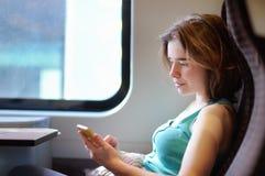 Πορτρέτο ενός όμορφου κοριτσιού που επικοινωνεί στο τηλέφωνο σε ένα αυτοκίνητο τραίνων στοκ φωτογραφία με δικαίωμα ελεύθερης χρήσης